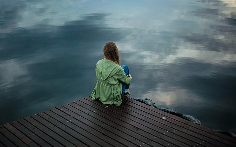 Depressed girl sat by a lake