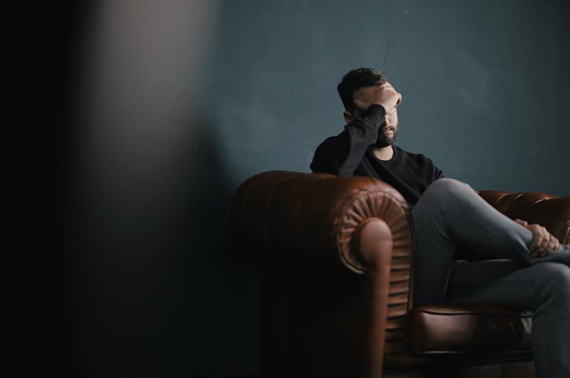 Man sat on sofa covering face, suffering with depression
