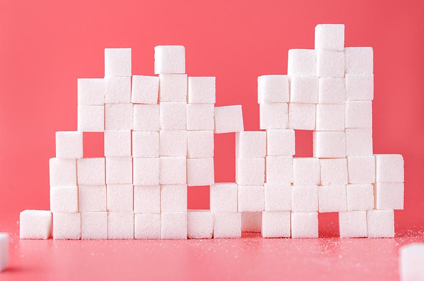 A pile of sugar cubes built into a wall against a pink background