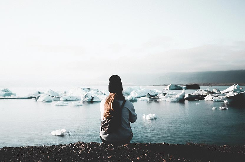 Lady sat on the shore of icy waters with icebergs