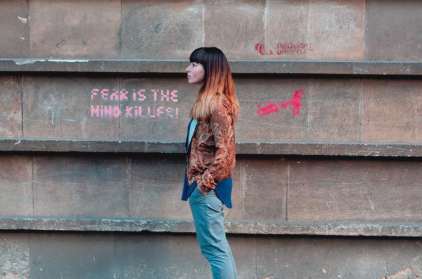 A lady stood still next to graffiti that reads 'Fear is the mind killer'.