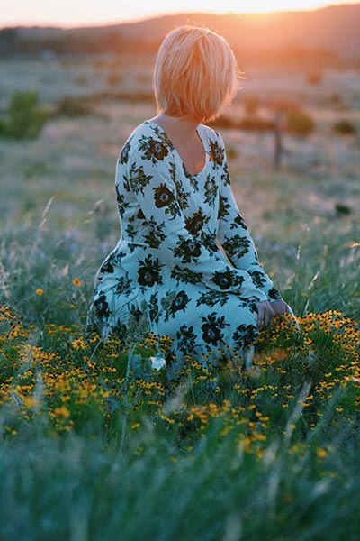 Lady in her late 30s or early 40s sat in a field looking at a sunset view