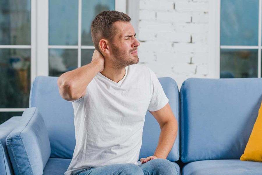Man on sofa holding his neck due to pain
