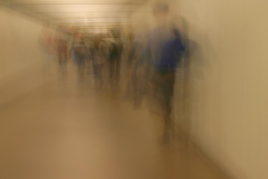 Image of people in a corridor, blurred, giving a sensation of dizziness