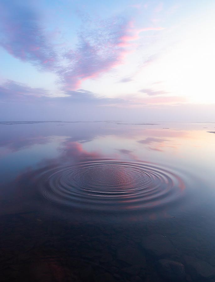 Image of sunrise over still water with ripples in a circle
